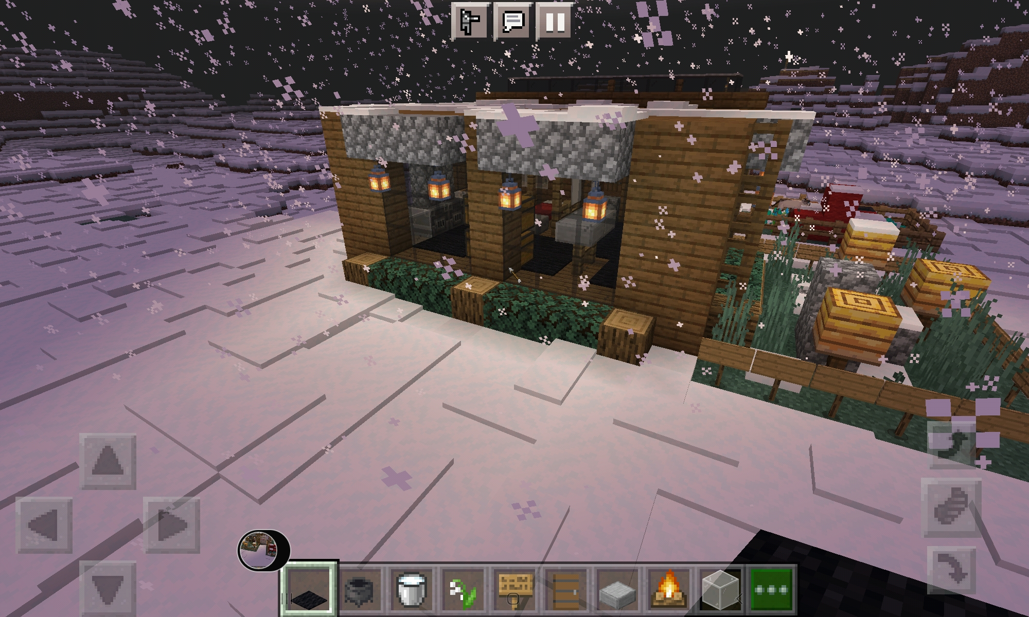 A small minecraft build of a modern cabin in the snow, featuring hanging lanterns and a small garden with bee hives.